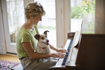Smiling mid-adult woman playing a piano with her pet dog on her lap.