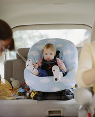 Portrait of a toddler sitting in a car seat in the back of her mother's car.