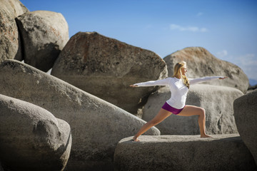 Active young woman practicing yoga on large rocks near the sea.