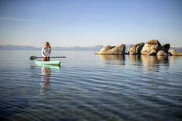 Active young woman paddleboarding across a lake.