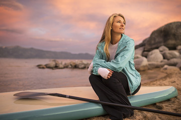 Young woman sitting on her paddleboard.