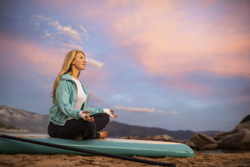Young woman meditating on her paddleboard.