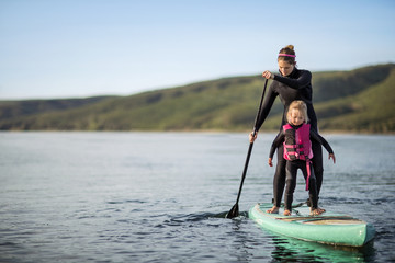 Young woman and her young daughter paddleboarding together on a lake.