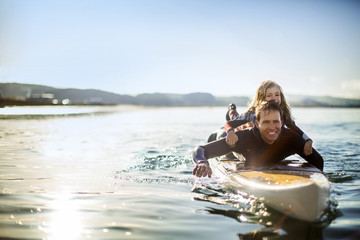 Smiling mid adult man paddleboarding with his young daughter.