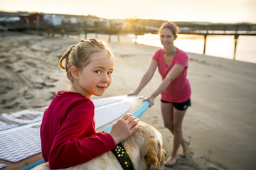 Portrait of a young girl at the beach with her mother and dog.