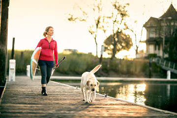 Mid adult woman walking with pet dog on wharf.
