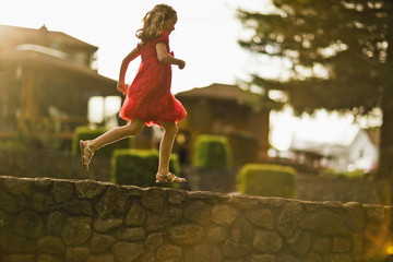 Young girl running along a stone wall.