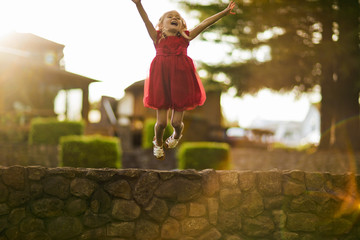 Young girl jumping off a stone wall.
