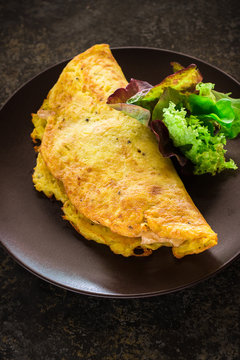 Omelet and green salad on ceramic plate.