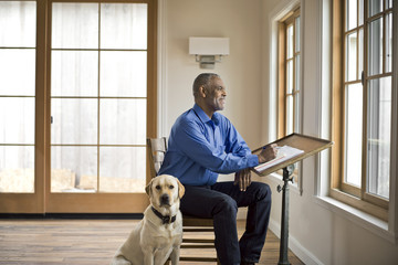 Smiling man sits at desk with dog and looks out of the window