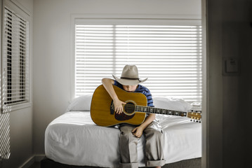 Young boy sitting on his bed with his acoustic guitar.