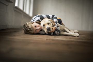 Loving young boy hugging his dog.