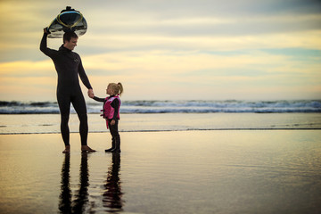Surfer holding hands with his young daughter at the beach.