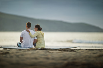 Couple sitting on a surfboard at the beach.