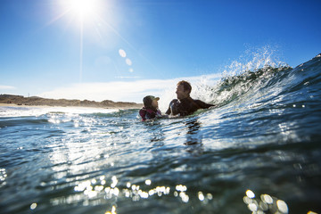 Father and daughter swimming in the surf.
