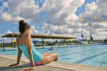 Young woman relaxing at the edge of a swimming pool.