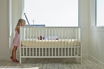 Young girl peeking into her baby sister's crib.