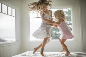 Smiling sister's jumping on bed at home