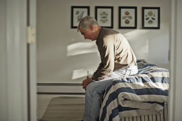 Depressed senior man sitting alone on a bed.