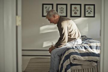 Depressed senior man sitting alone on a bed.