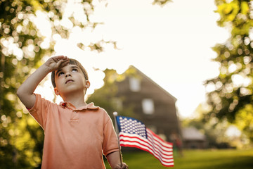 Young boy saluting while holding an American flag.