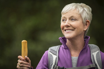 Happy mature woman enjoys a peaceful hike through the woods.