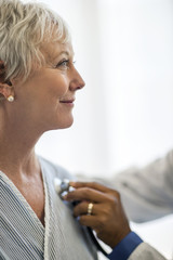 Smiling mature woman has her heartbeat listened to by the doctor.