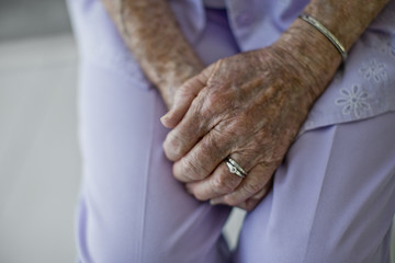 Hands of an elderly woman clasped in her lap.