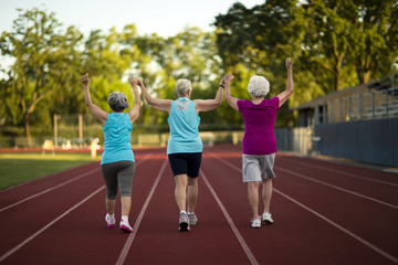 Senior women holding hands while walking on an athletic track.