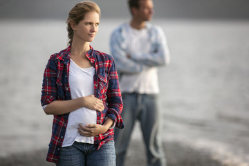 Pregnant woman gently holds her stomach on the beach while her husband stands behind her.