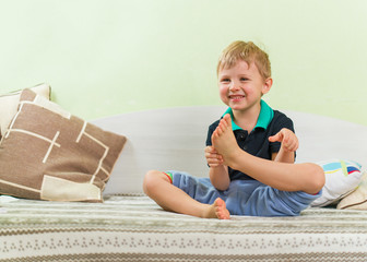 Cute blond kid has fun playing yoga, with a broad teeth smile on his face. Sitting on the children's bed. Dressed in a casual black shirt and blue pants, bare feet. Looking ahead.