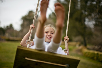 Happy young girl swinging on a wooden rope swing.