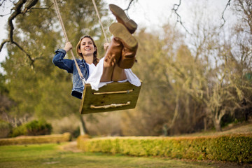 Happy young woman swinging on a wooden rope swing.