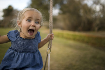 Portrait of a little girl playing on a swing in the back garden.