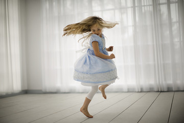 Little girl joyfully spinning around in bare feet in an empty room.