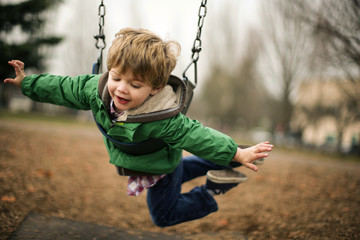 Happy young boy playing on a chain swing at a park.