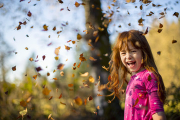 Smiling young girl having fun playing in autumn leaves.