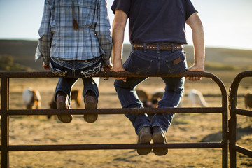 Farming couple sit side by side on a fence on their ranch.