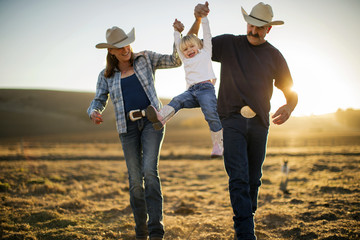 Farmer and his wife swinging their daughter into the air between them on their ranch at sunset.