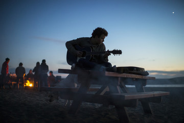 Guitar player sitting on a picnic table at the beach at sunset.