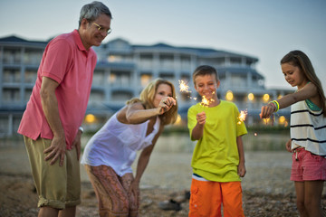 Happy smiling family having fun with sparklers on the beach at sunset.
