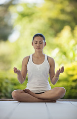 Relaxed young woman meditating on a deck.