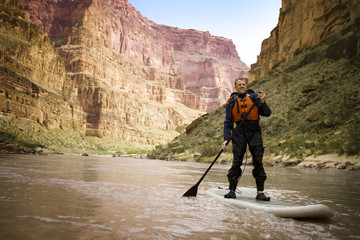 Mid adult man paddleboarding on a river.