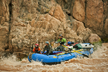 Group of friends white water rafting together through rapids in a fast flowing river.