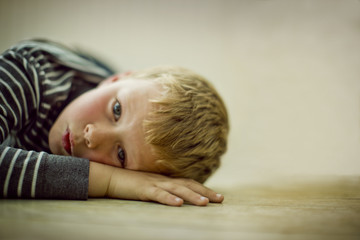 Portrait of a young boy lying on the floor.