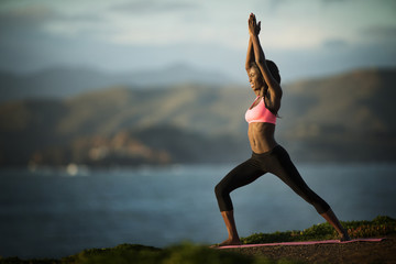 Young woman standing in a yoga pose near a coastline.