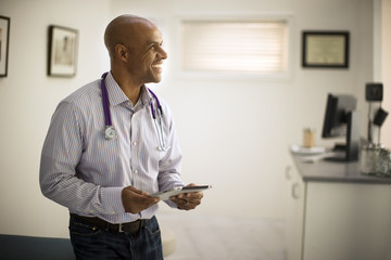 Smiling mid adult doctor holding a digital tablet.