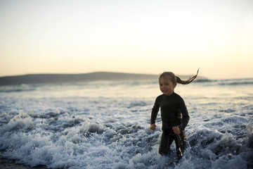 Young girl playing in the surf at sunset.