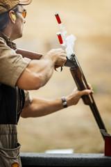 Man shooting a gun at a firing range.