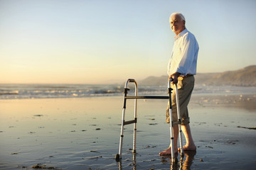 Portrait of a senior man standing on a beach with a walking aid.